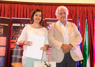 Sara Mezquita receiving from Angel G. Piñero a gift for her participation